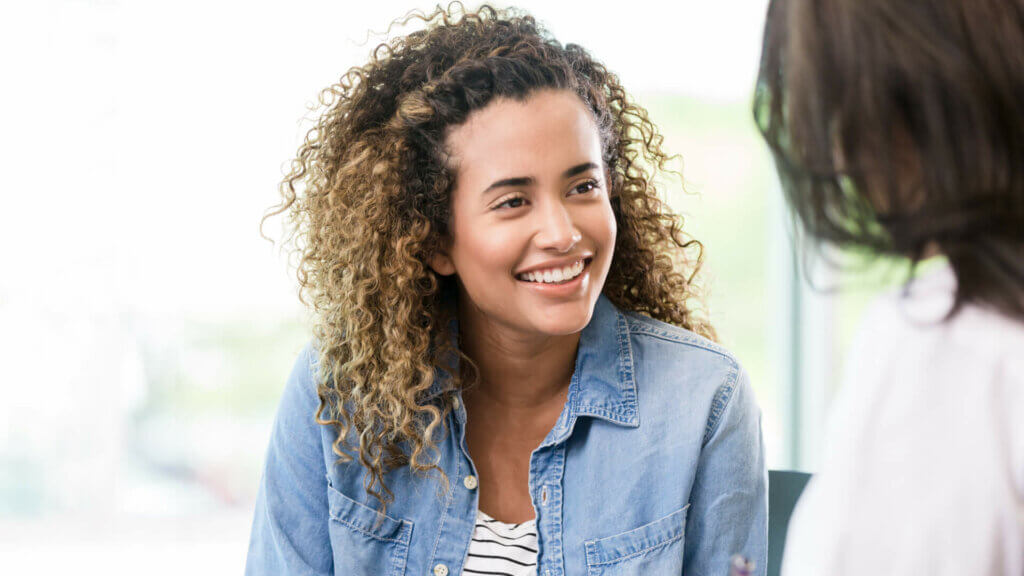 smiling-young-woman-wearing-white-and-grey-striped-shirt-and-blue-denim-jacket-sitting-near-window-with-woman-gynecologist-in-foreground-speaking-about-endometritis-diagnosis