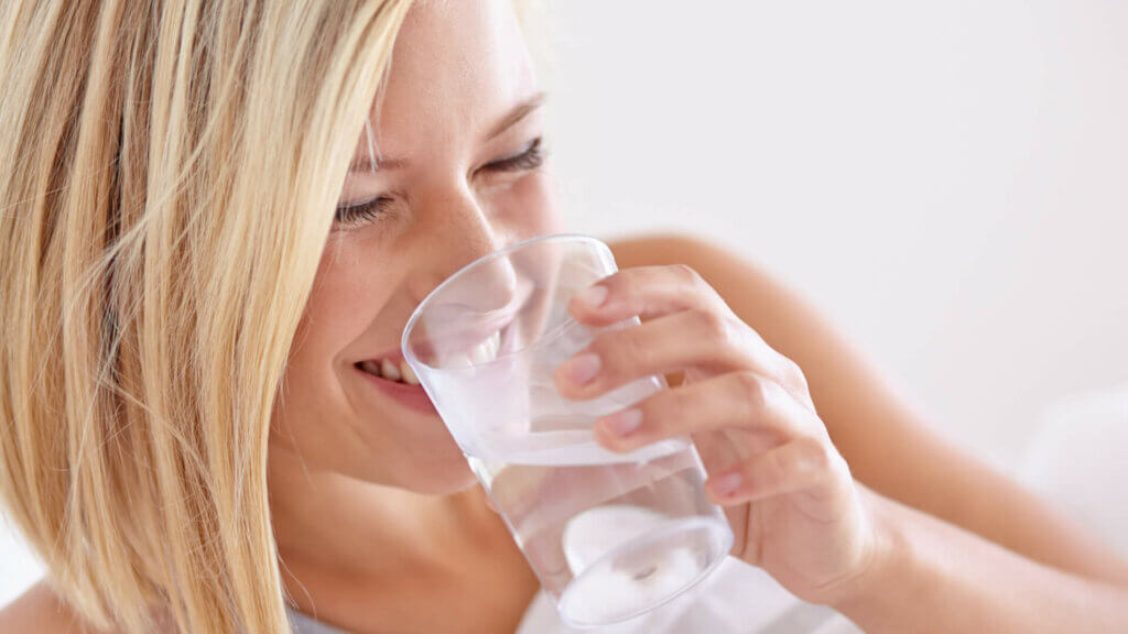 young-woman-smiling-while-holding-glass-of-water-with-inositol-powder-supplement-mixed-in-up-to-mouth