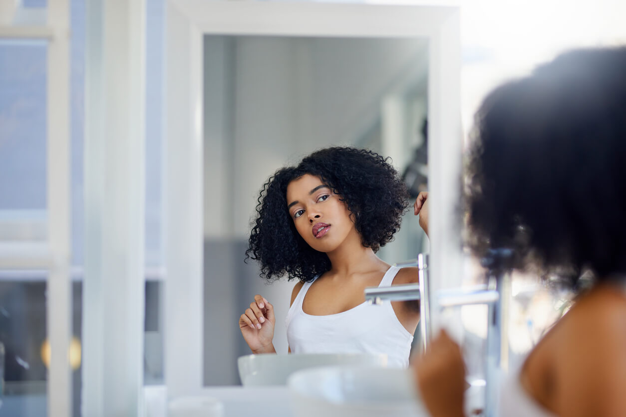 young-woman-with-curly-black-hair-wearing-white-tank-top-looking-at-herself-in-the-bathroom-mirror
