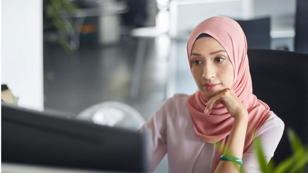 A young woman wearing a light pink hijab and pink blouse resting her chin on her hand while working at a computer