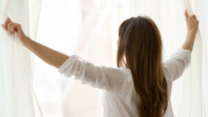 woman-with-long-brown-hair-wearing-white-shirt-while-opening-gauzy-white-curtains-in-sunlight
