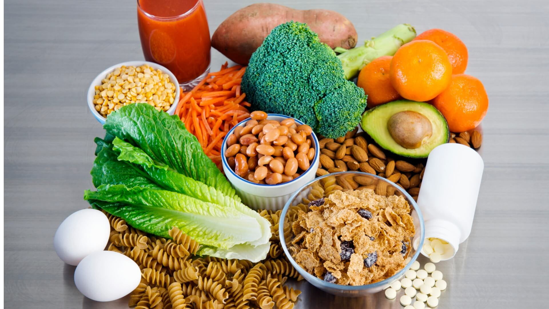 An arrangement of foods high in folate including pasta, broccoli, eggs, avocado, and a bottle of supplements