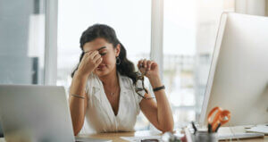 A young, professional woman sitting at a desk in a sunny office and holding the bridge of her nose with one hand to relieve hormonal headache pain.