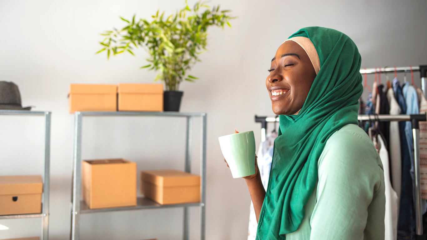 A smiling woman wearing a green headscarf and holding a mug of tea while sitting in a retail shop.