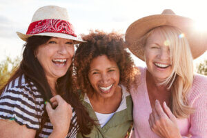 three middle-aged women laughing together outdoors