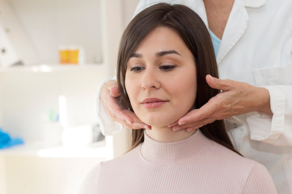 Woman being examined by a doctor for throat and thyroid problems