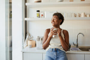 Happy black woman taking a supplement drink at home