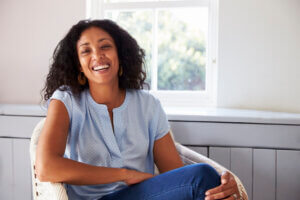 Happy Black woman of perimenopausal age sitting at home