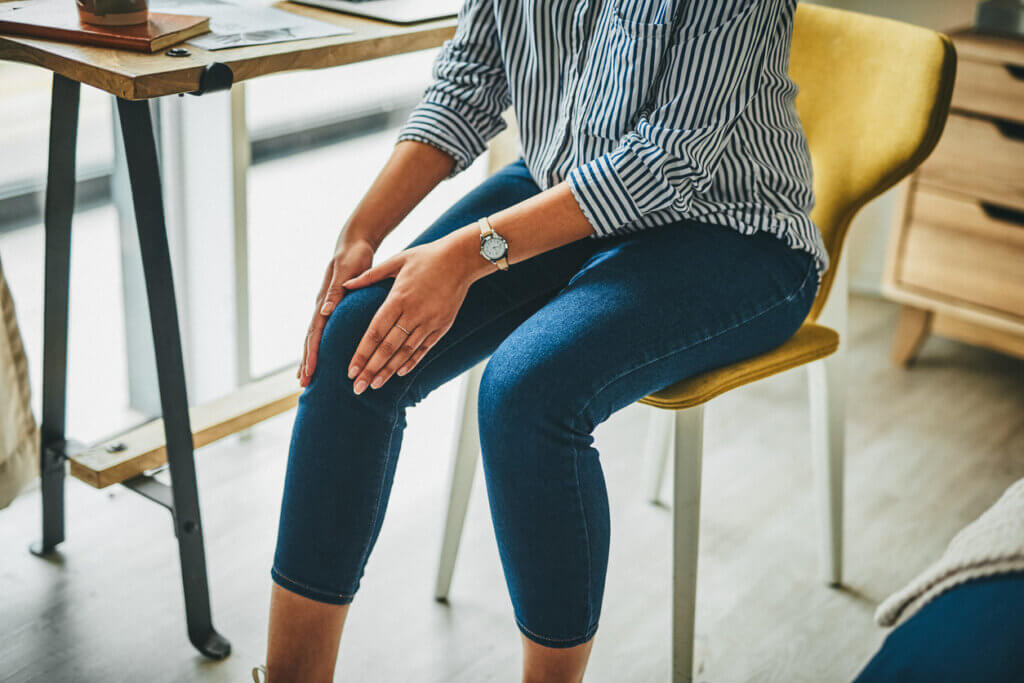 Joint pain menopause symptoms; woman rubbing her painful knee